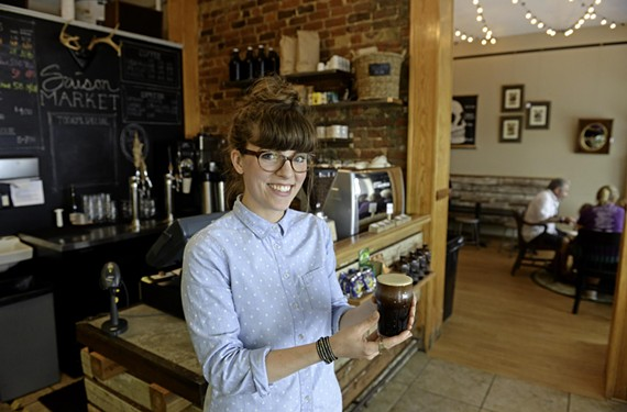 Colby Beck, a barista at Jackson Ward's Saison Market, offers a mug of the explosively named nitro coffee — you can get caffeinated here from morning to midnight along with breakfast, lunch or dinner.