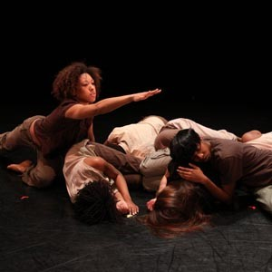 """Courtney Cook reaches out as her fellow VCU dance students (Jasmine Domfort, Jaime Dzandu, Alyssa Gregory, Ronnique Murray, Kim Palmer) slumber. It's a key movement in Jawole Willa Jo Zollar's """"Shelter,"""" an acclaimed dance performance that will be the centerpiece of this week's VCU Dance Now concert at Grace Street Theater. Photo by Sarah Ferguson"""