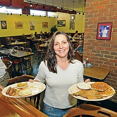 Dionna Kelleher, two years into ownership of long-running McLean's Restaurant, serves breakfast plates at its new Museum District location.