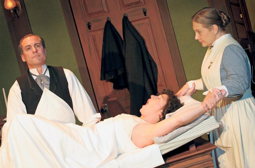 Dr. Givings (Larry Cook) prepares to treat a patient (Laine Satterfield) for hysteria as Annie the nurse (Lauren Leinhaas-Cook) looks on. The Victorian-era vibrator used on set was found in a Petersburg antique shop for $15. - JAY PAUL