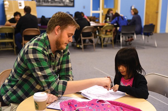 Every Wednesday, Tabernacle sends buses around the metro Richmond area to pick up refugee children for an after-school program that includes one-on-one tutoring.  Here, Jeff Walton, a 26-year-old seminary student, works with Shee Gay Moo. - SCOTT ELMQUIST
