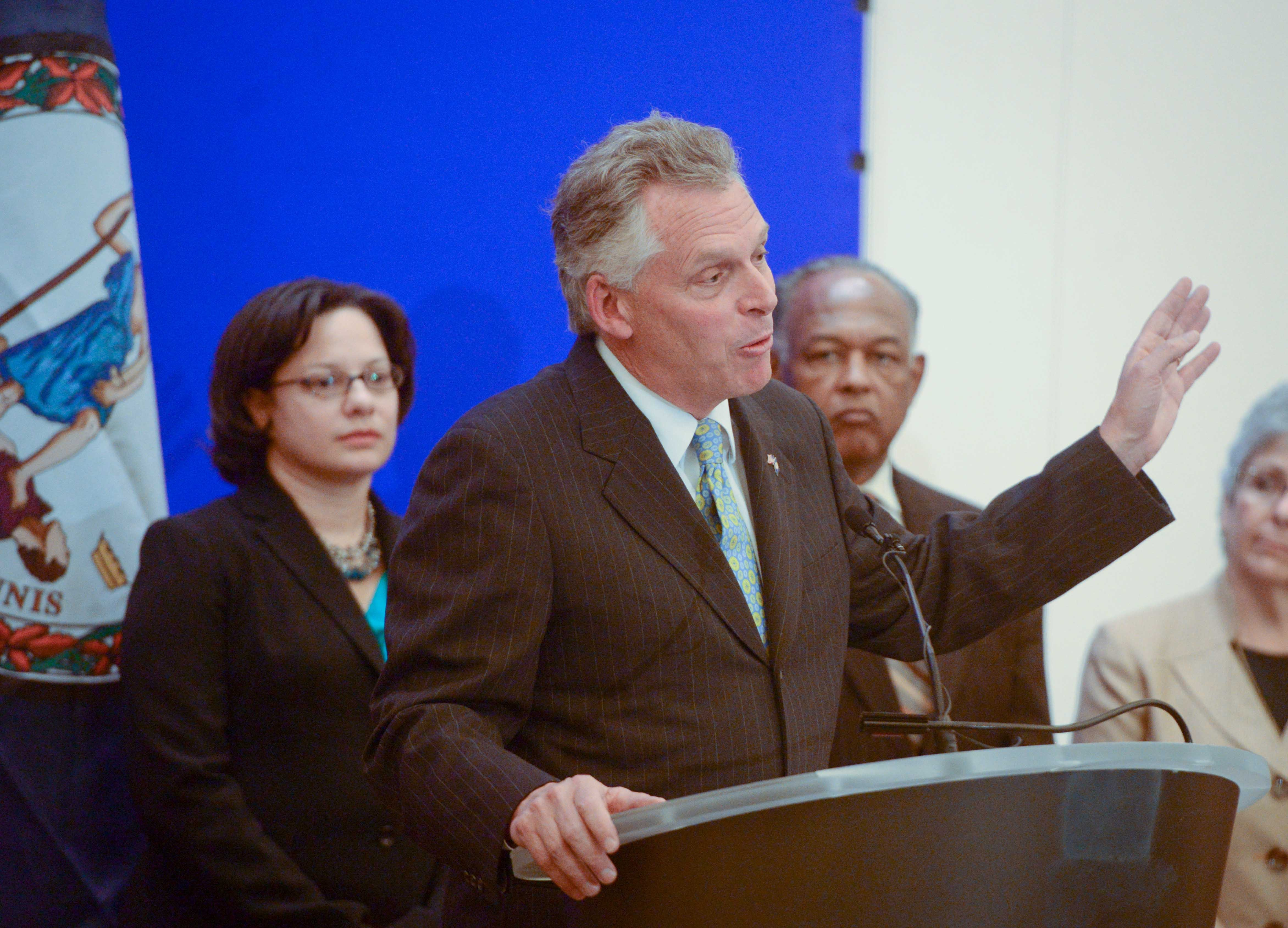 Flanked by Richmond Delegate Jennifer McClellan and Mayor Dwight Jones, Terry McAuliffe speaks to reporters at the Capitol in Richmond Wednesday. - SCOTT ELMQUIST