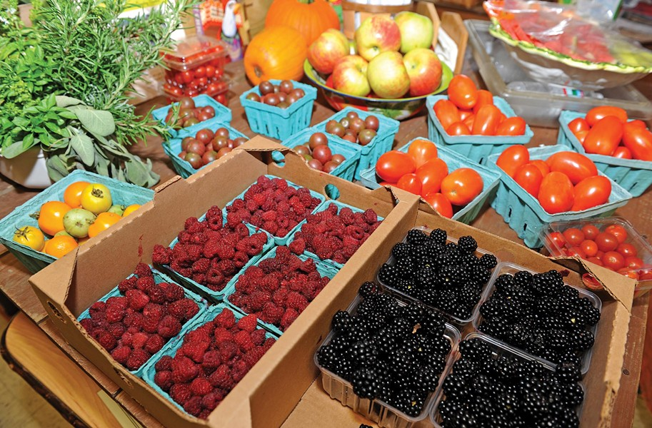 Fresh produce and fruit are displayed on tables at Farm to Family on the Mechanicsville Turnpike across from Roses. The for-profit farm stand was founded by Mark Lilly and Suzi Miles-Lilly, below. They've found a dedicated following since opening four years ago, they say, and that educating people about the food they sell is critical to increasing demand for it.