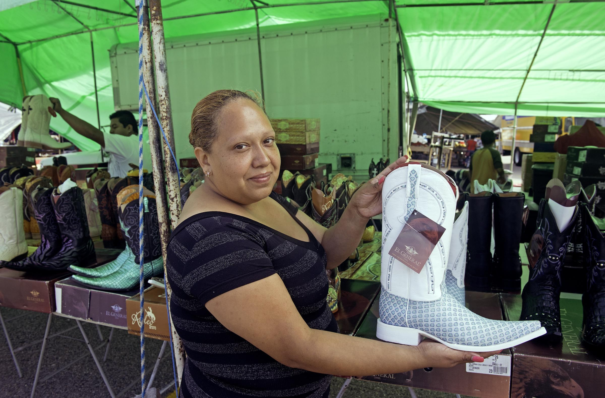 Gloria Rodriguez holds one of the Mexican cowboy boots her family has sold at Bellwood for 11 years. During the week, she works at a hotel; her husband works construction. - SCOTT ELMQUIST