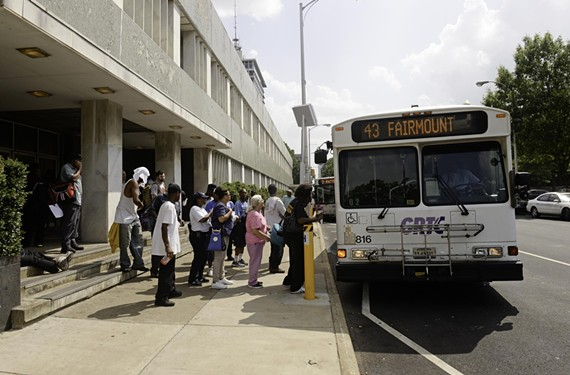 GRTC bus riders board at the temporary transfer plaza near the decaying Public Safety Building on North Ninth Street.