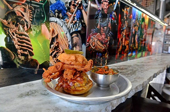 Gwarbar makes food the way the band, Gwar, performs its shows — over the top. Presenting the Baconecutioner: A heart stopping combination of bacon, cheddar, bacon aoli, beer-battered bacon and bacon-onion jam with collard greens.