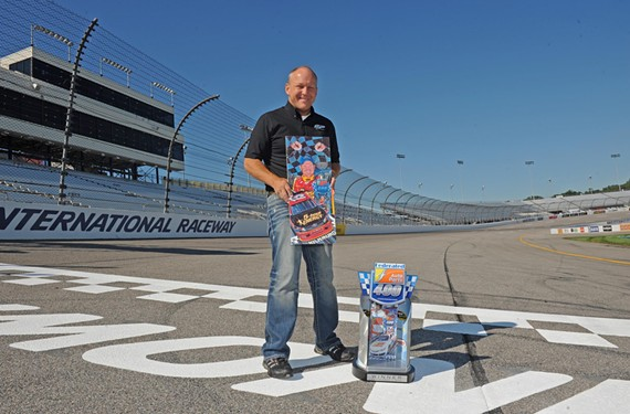 Hopewell native Sam Bass stands at Richmond International Raceway with one of his official NASCAR drawings and the trophy he designed. - SCOTT ELMQUIST