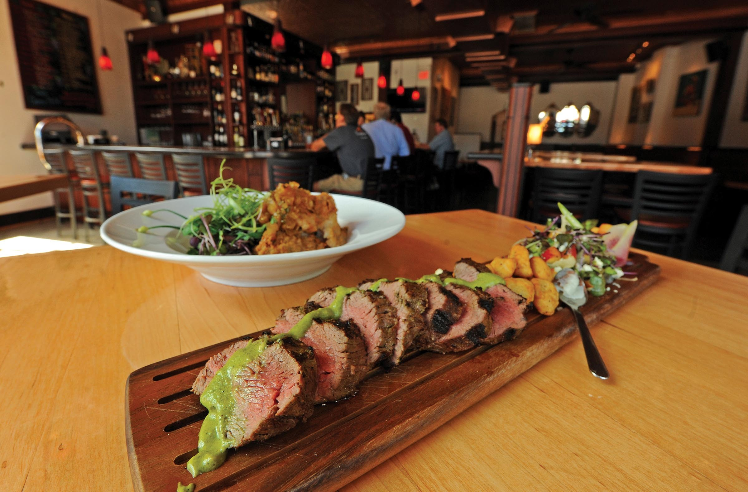 In the foreground, sliced filet of Angus shoulder chimichurri is served with gold gnocchi in bone marrow and a salad of arugula, fennel and grilled nectarine. Behind that, fried pork cheeks with green tomato marmalade are paired with white cheddar corn bread pudding and pickled baby black kale with corn shoots at the Viceroy in the Museum District. - SCOTT ELMQUIST