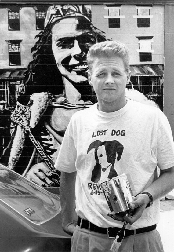 In this 1997 photo, Trask poses with the mural he painted on the side of Sidewalk Cafe on Main Street. - FILE PHOTO BY JAY PAUL
