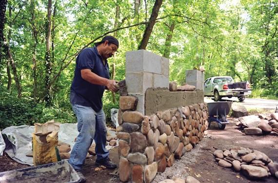 J. Refugio Hernandez Gonzalez works on the new stone entrance sign at Pony Pasture Rapids, the city park along the James River on Riverside Drive. - SCOTT ELMQUIST