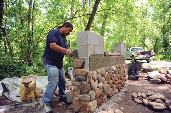 J. Refugio Hernandez Gonzalez works on the new stone entrance sign at Pony Pasture Rapids, the city park along the James River on Riverside Drive. - SCOTT ELMQUIST