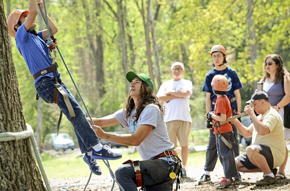 """Jason Anderson of Riverside Outfitters guides Chesterfield County youth up an 85-foot tall northern red oak along the James River on Saturday. They climbed to about 55 feet. """"I've gotten pretty good at encouraging kids to get over their fears,"""" he says. """"They did great."""""""