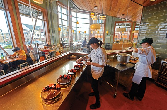 Laura Boehmer, left, and Molly Berg decorate cakes inside Whole Foods Market. Its bakery and cafe overlook townhouses beyond. - SCOTT ELMQUIST