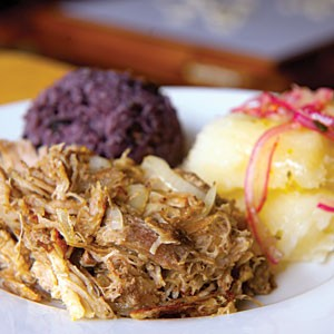 Lechon asado, pork roast marinated in mojo criollo, is served with arroz morro and yuca con mojo at Kenn-Tico, a new Cuban eatery downtown.
