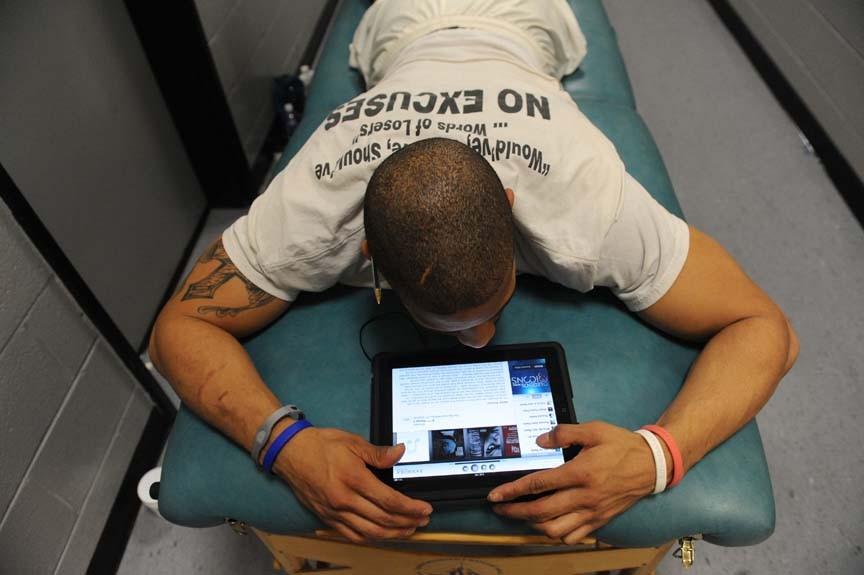 Linebacker Louis Corum gets a pre-game massage outside the Raiders locker room, biding time with his iPad. - SCOTT ELMQUIST