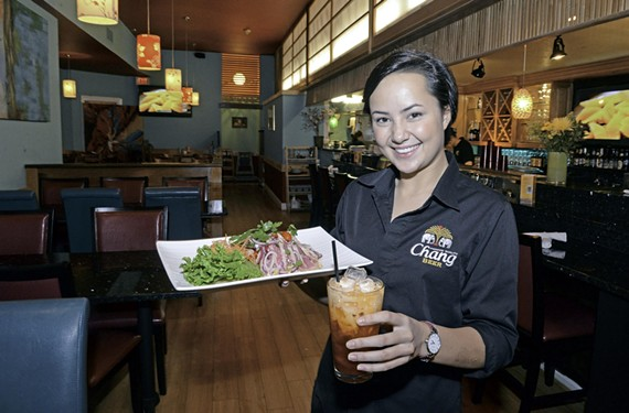 Lorna Bedford, daughter of owner Sunisa Bedford, holds tuna num tok and Thai iced tea.