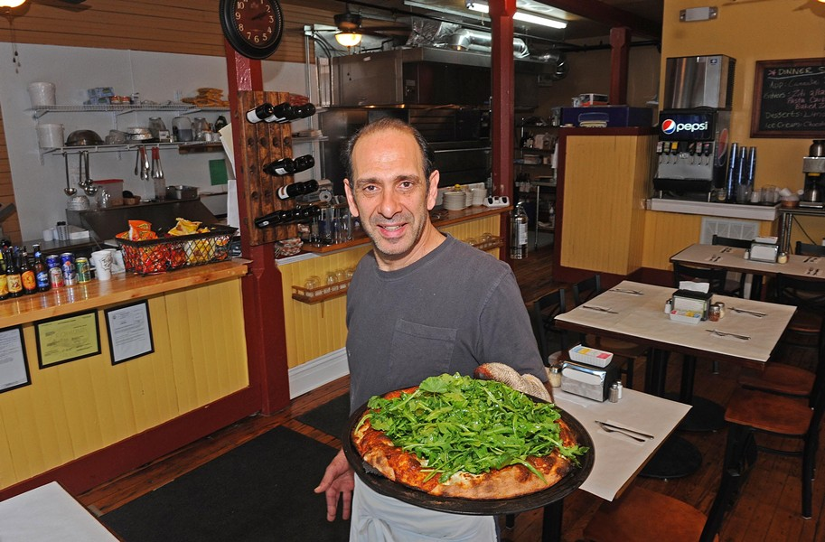 Michael Calogerakis shows the white pizza with arugula, lemon oil, ricotta and mozzarella at his Church Hill business, Anthony's on the Hill. - SCOTT ELMQUIST