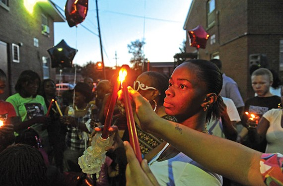 Mourners light candles at vigil for Robert L. Poag, who was killed in September.
