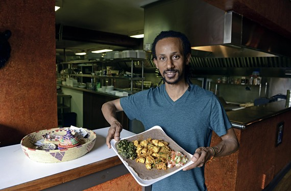 Nile's Yoseph Teklemarian shows off dono tibs, chicken breast with garlic, onions, jalepeños and rosemary, served on top of Ethiopian staple, injera.