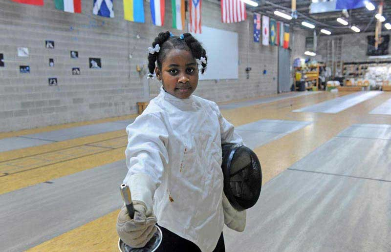 Nygeria Jiggetts, 9, poses with her fencing equipment in the Richmond Fencing Club's salon. - SCOTT ELMQUIST