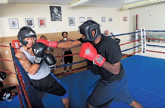 One of coach Royster's most promising young fighters, Freddie Lee Bell III, hits Justin Booker with a hard right during a sparring match. - SCOTT ELMQUIST