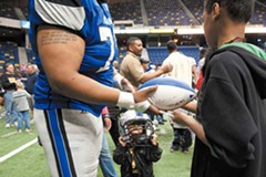 One of the main attributes of arena football: Fans are allowed onto the field after games. Dwayne Delaney signs a football for a young fan. - SCOTT ELMQUIST