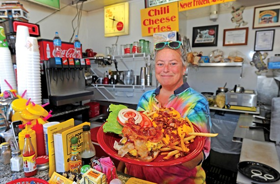 Owner Melody Walden presents the bacon inside-out cheeseburger with bacon cheese fries at the Northside business Pop's Dogs & Mom's Burgers on Brook Road.