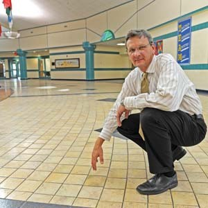 P. Andy Hawkins, chief operating officer for finance and operations at the Richmond Public Schools, shows off the newly cleaned and coated tile floors at Lucille M. Brown Middle School. Photo by Scott Elmquist