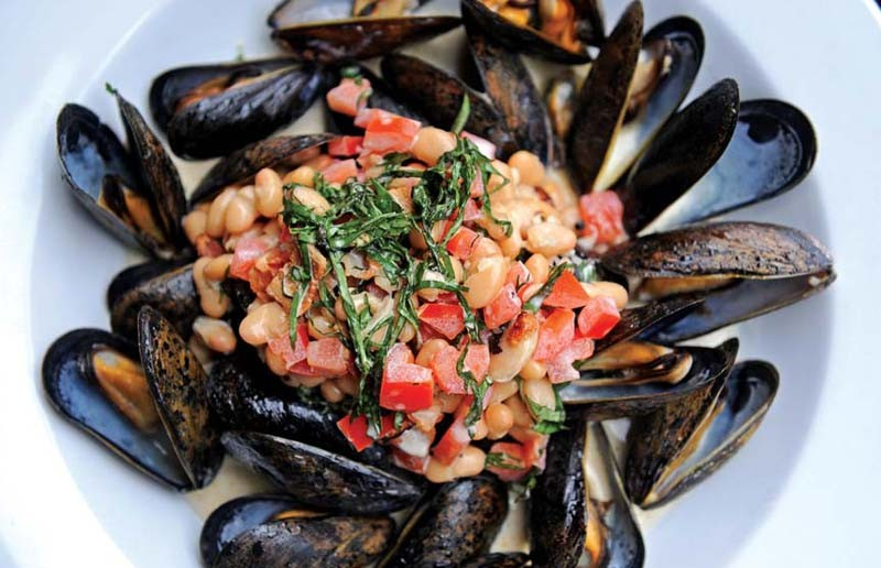 Prince Edward Island mussels are served with bacon, beans, garlic, tomatoes and  white wine basil cream at M Bistro in Rocketts Landing. - SCOTT ELMQUIST
