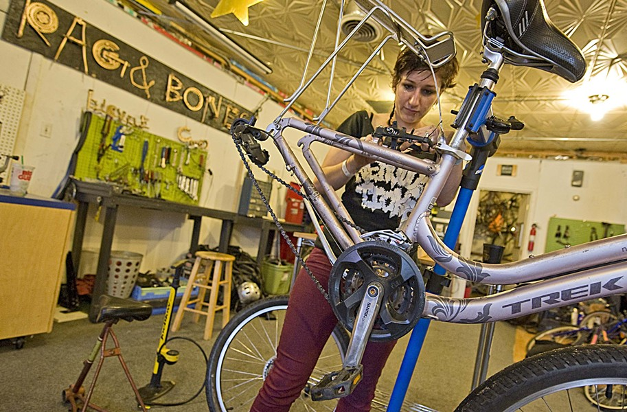 Rag & Bones Bicycle Co-op staff member Sera Stavroula works on a bike in the Scott's Addition business. It's staffed by volunteers who offer space and repair help. - ASH DANIEL