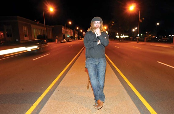 Rand Burgess, owner of the Camel restaurant in the 1600 block of West Broad Street, now must routinely take to the median to warn customers not to park on the street. - SCOTT ELMQUIST