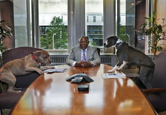 Richmond Mayor Dwight Jones sits in his conference room with two dogs. Rachel Day, a recent VCU graduate, donated her services as a photographer for the fundraising calendar.