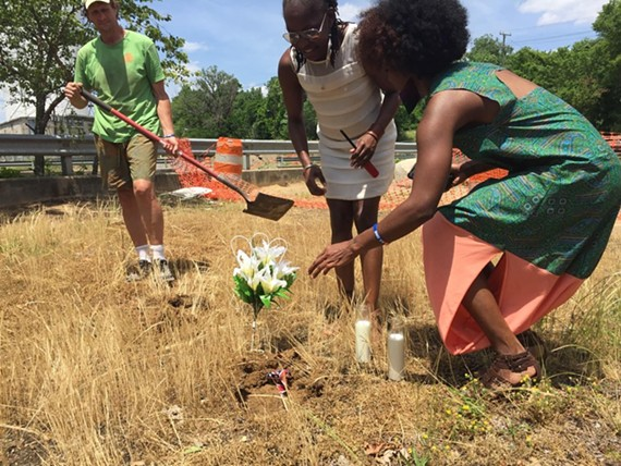 Rick Tatnall looks on as Darlene Anita Scott and Evandra Catherine bury a Confederate flag. - SCOTT ELMQUIST