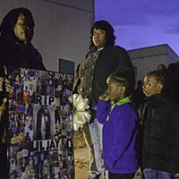 Scenes from the Vigil for Jayquan Powell Rosalyn Powell, the mother of murder victim, Jayquan Powell, holds a collage of photographs as her grandson Kahman Gayles, 4, stares on, at a vigil in his dad's honor.