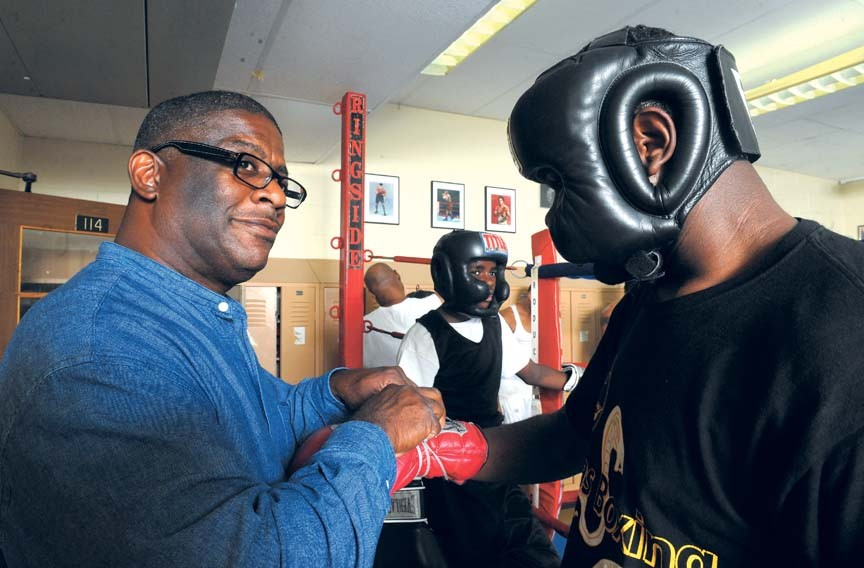 Royster readies Freddie Bell for a sparring match at his gym on the North Side. - SCOTT ELMQUIST