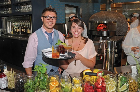 Ryan Jones and Lauren Spain show a blackberry mojito, an old fashioned, and a pure and simple from the bar, which faces Tazza Kitchen's central feature, a wood-fired oven. - SCOTT ELMQUIST