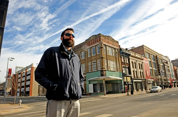 Ryan Rinn stands near 300 E. Broad St., which was transformed by volunteers last fall. They washed awnings, painted facades and hung new signs in the spirit of community design.
