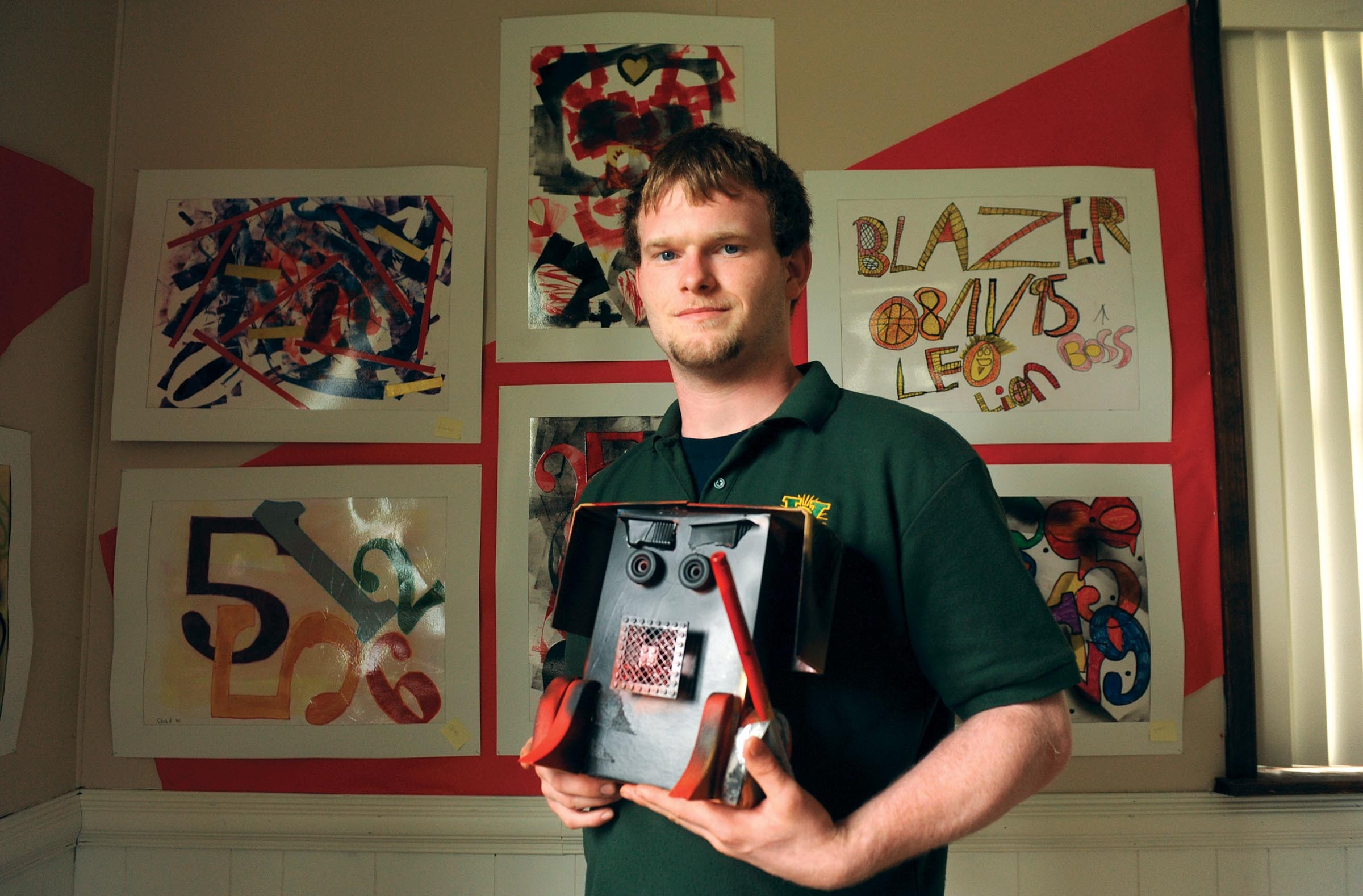 """Senior student Michael Rhoades holds up an art project he made for his father inspired by Darth Vader of """"Star Wars"""" fame. Behind him hang paintings from other art students at the alternative John G. Wood School. - SCOTT ELMQUIST"""