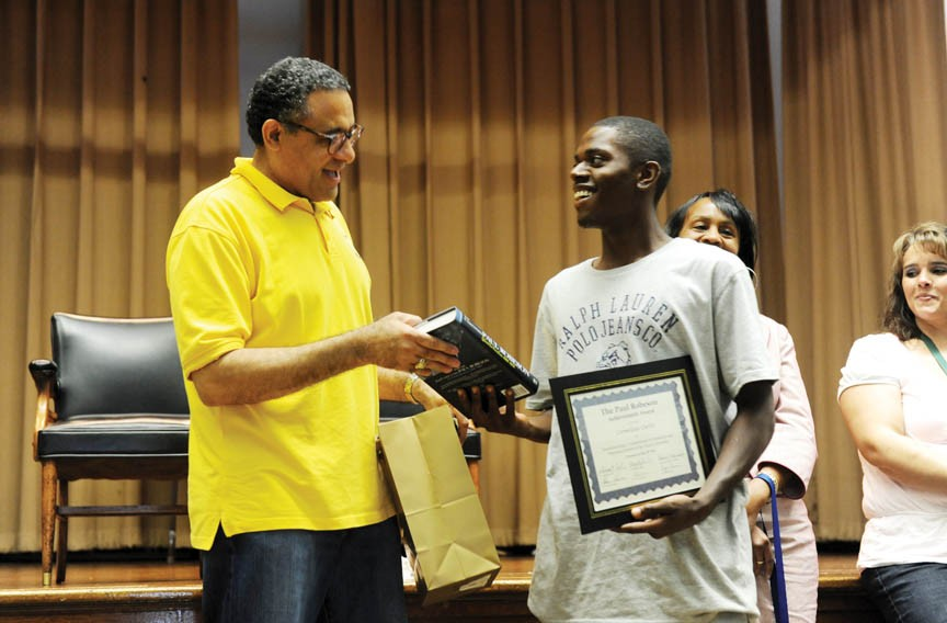 Sherman Carroll, academic coordinator for the learning center at the Adult Career Development Center, gives Cornelius Curtis the program's Paul Robeson Achievement Award for academic and personal growth in the face of adversity. - SCOTT ELMQUIST