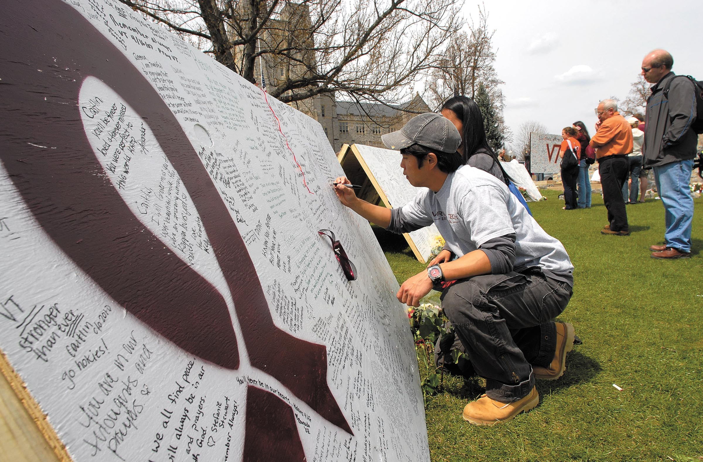 Simon Chang, a 2006 graduate of Virginia Tech, leaves his condolences on a memorial after 32 people were shot and killed there in April 2007. The tragedy prompted calls for improvements to the mental health system. - SCOTT ELMQUIST