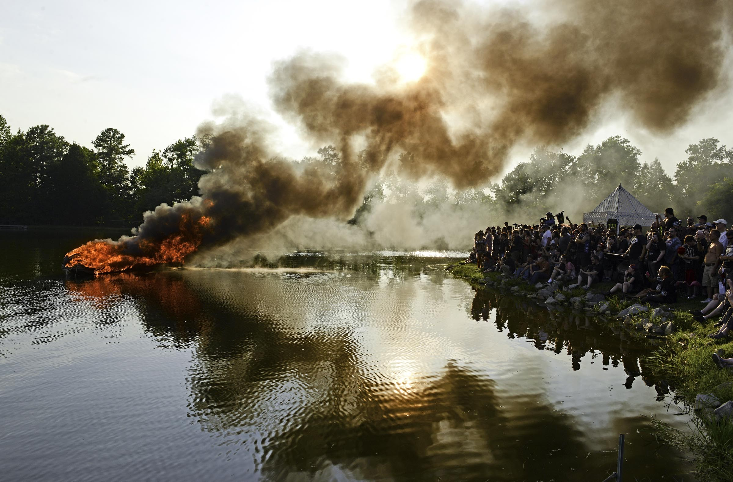 Smoke billows from a boat carrying the empty costume of the late Dave Brockie, who played Gwar frontman Oderus Urungus. The Viking-style ceremony brought thousands of fans to Hadad's Lake in Henrico on Aug. 15. - SCOTT ELMQUIST