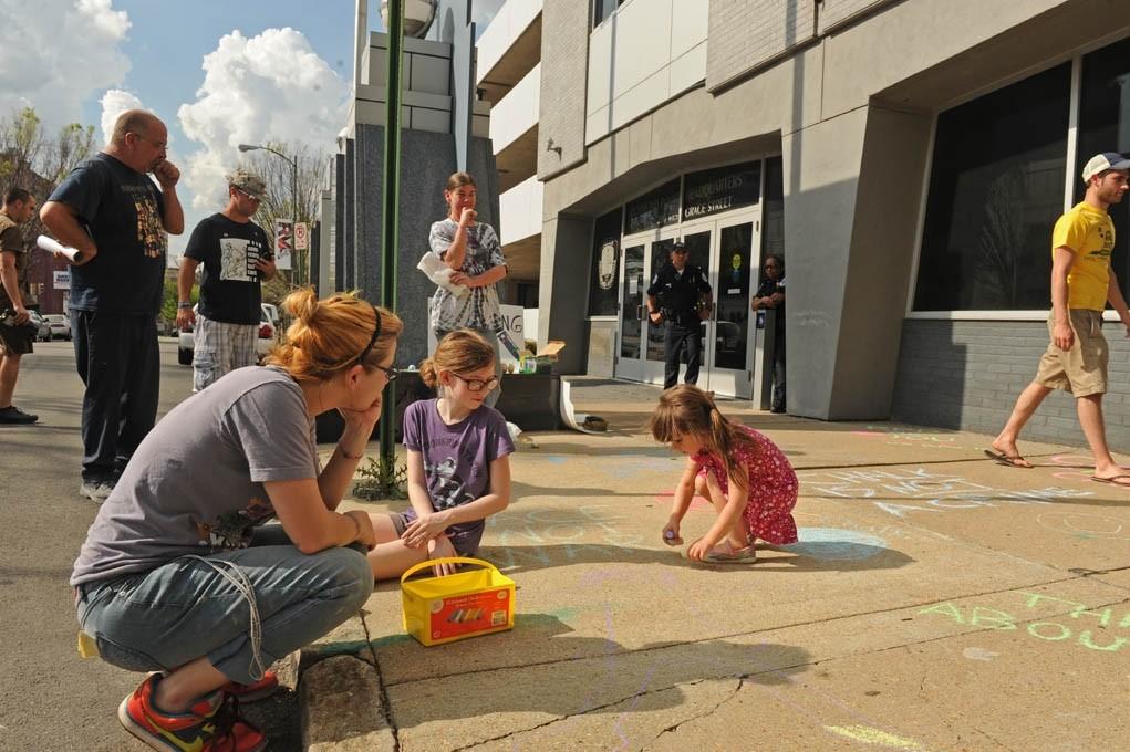 Susan Mortensen (left) watches her daughter Ava, 4, draw on the sidewalk outside police headquarters. - SCOTT ELMQUIST