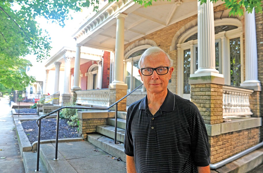 Tabernacle Baptist Church member Nelson Melton in front of two vacant early 20th-century houses the church owns and plans to raze as part of a $2 million renovation. - SCOTT ELMQUIST