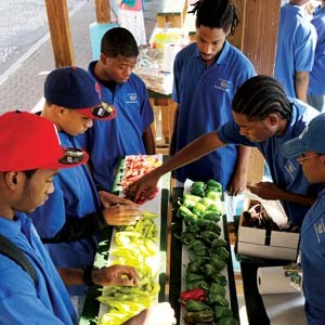 Teenagers from the Mayor's Youth Academy gather around their produce stand at the 17th Street Farmers' Market. Photo by Scott Elmquist.