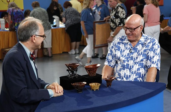 The guy on the right looks happy because veteran Roadshow Asian arts expert Lark Mason just identified his collection of late 17th- or early 18th-century Chinese carved rhinoceros horn cups as worth $1 million or more. - ANTIQUES ROADSHOW