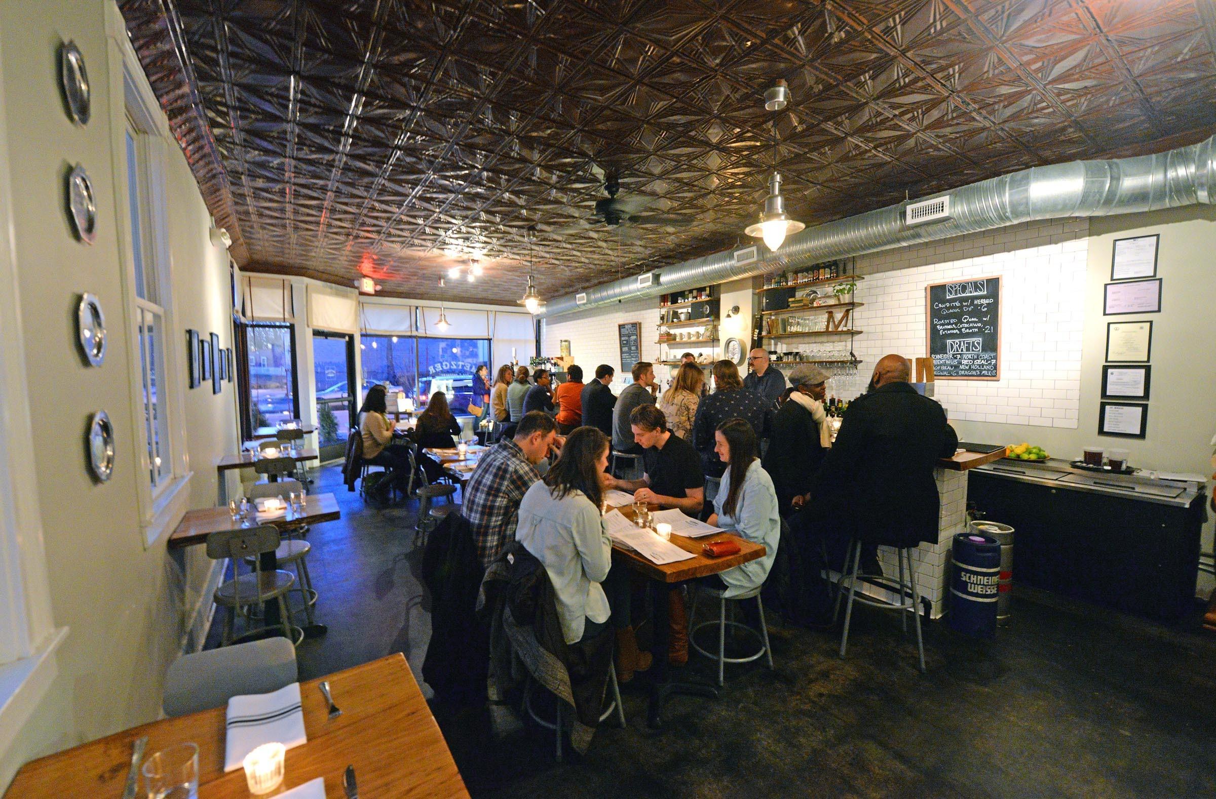 The restaurant's simple interior features white subway tile and wood floors. - SCOTT ELMQUIST