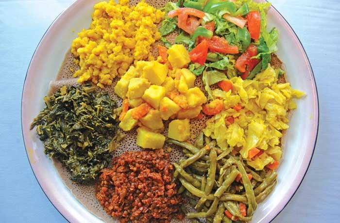 The veggie combo six at Addis has cabbage, potatoes, collards, lentils, yellow split peas and string beans on injera. - SCOTT ELMQUIST
