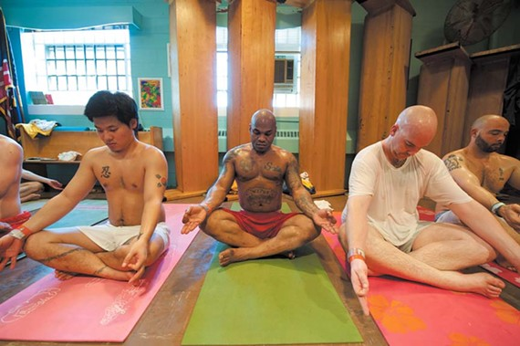 To make room for their yoga class, inmates upend the pews in the jail's Redemption Chapel and unroll their mats on the floor. From left: Chong Mounce, Calvin Faulk and Jay Stelter. - SCOTT ELMQUIST