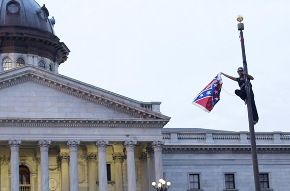 Activist Bree Newsome reaches her apex, taking down the Confederate battle flag at the South Carolina Statehouse on June 27. New Richmond resident Trevor FitzGibbon helped guide her group through the ensuing media blitz. - REUTERS/ADAM ANDERSON