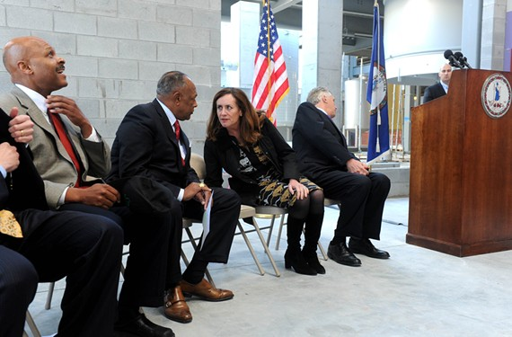 Dorothy McAuliffe talks to Richmond Mayor Dwight C. Jones last month during an event marking construction progress at Stone Brewing Co. in Fulton Bottom. The governor is at right and Maurice Jones, the state secretary of commerce and trade, is at left. - SCOTT ELMQUIST